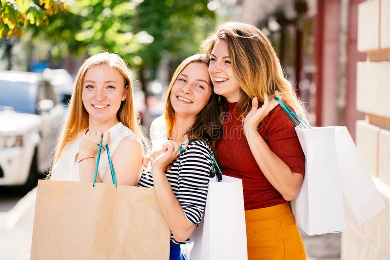 Amici femminili emozionanti con i sacchi di carta in mani immagini stock