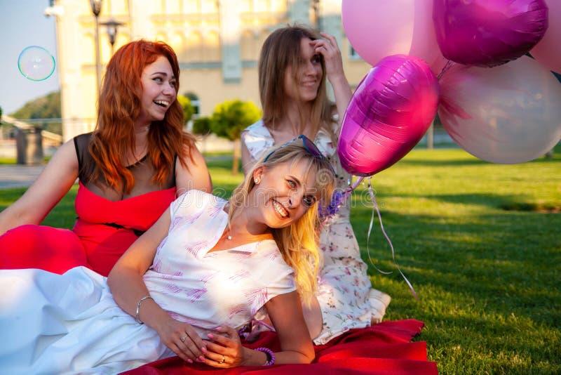 Amici femminili felici che giocano e che si divertono nell'erba verde immagine stock
