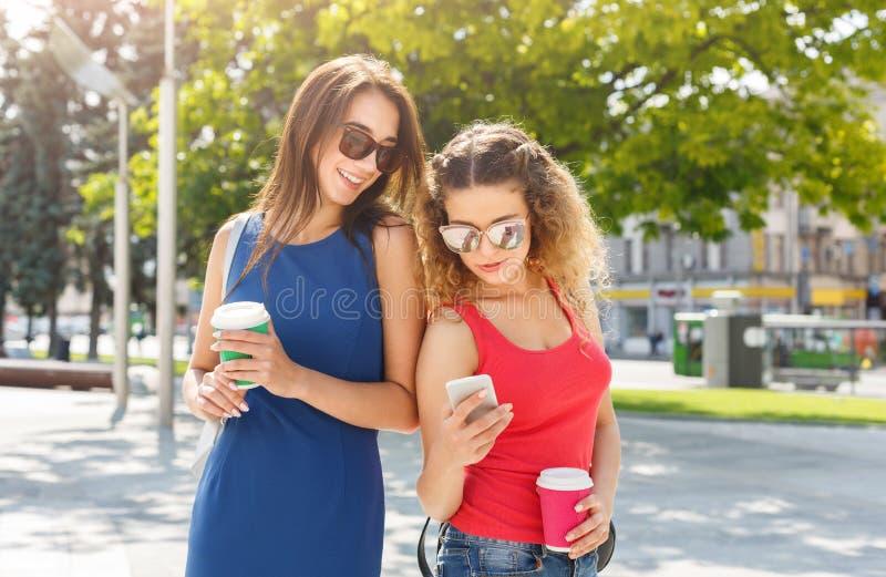 Amici femminili felici con lo smartphone all'aperto fotografia stock