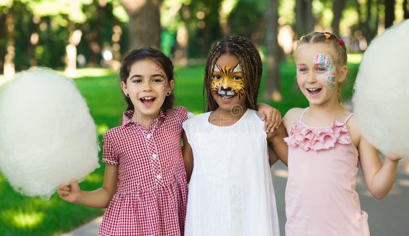 Amici femminili felici in parco di divertimenti con lo zucchero filato immagini stock libere da diritti