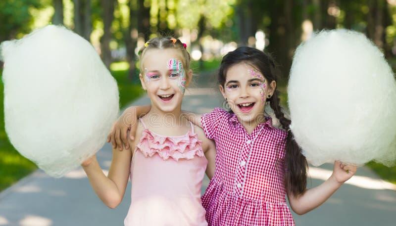 Amici femminili felici in parco di divertimenti con lo zucchero filato fotografia stock