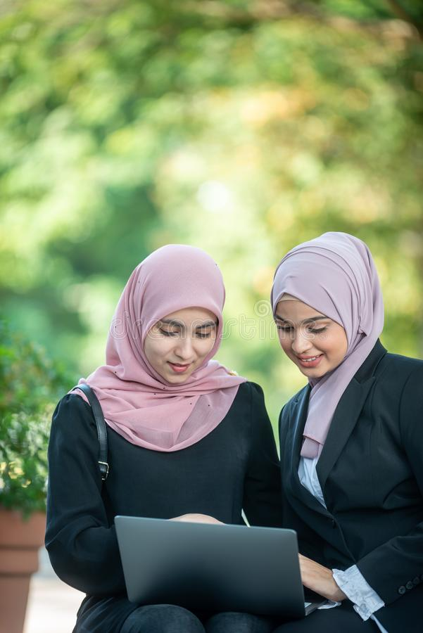 Amici femminili musulmani che esaminano insieme un computer portatile fotografia stock