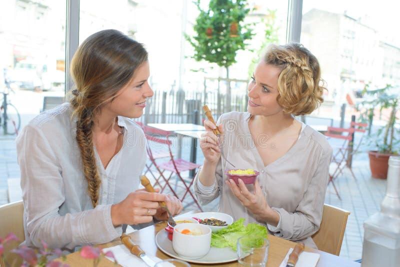 Amici femminili pranzando insieme al ristorante fotografia stock