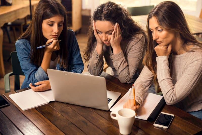 Amici femminili preoccupati con gli esami finali fotografie stock