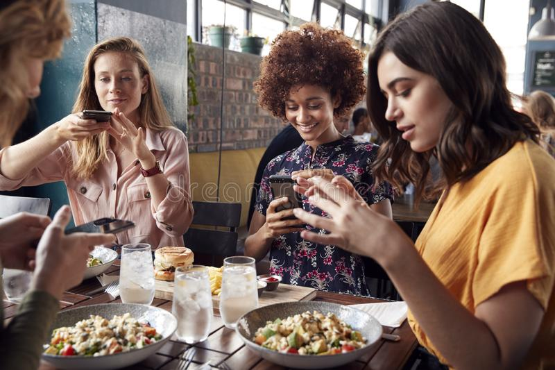 Amici femminili in ristorante che prende immagine di alimento in ristorante per inviare sui media sociali immagine stock