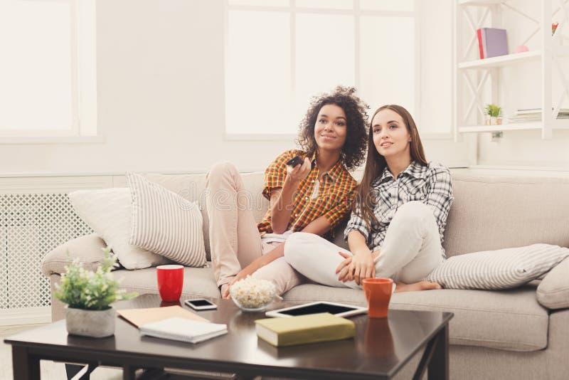 Amici femminili sorridenti che guardano TV a casa fotografie stock libere da diritti