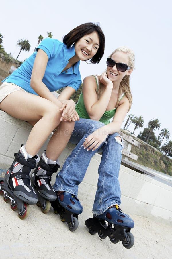 Amici femminili sui pattini di rullo immagine stock