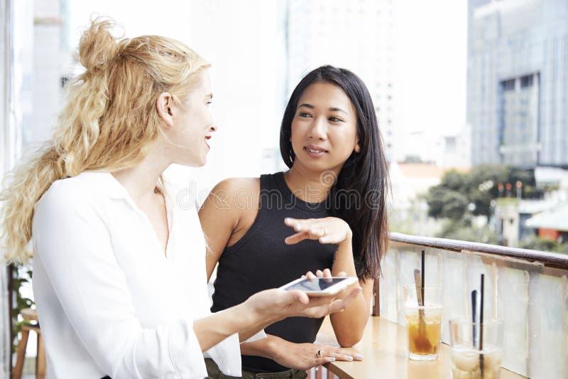 Amici femminili sul balcone del caff? fotografia stock libera da diritti