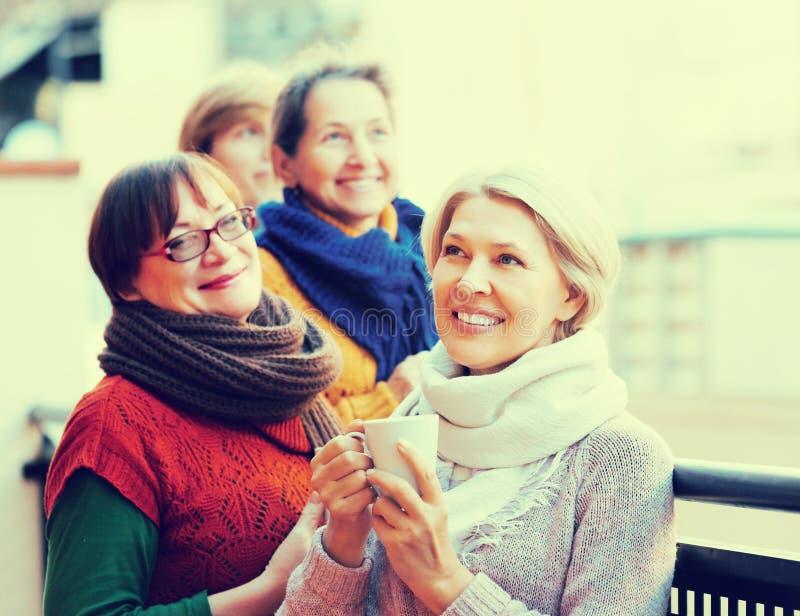 Amici femminili sul terrazzo di estate immagine stock