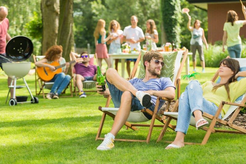 Amici giovani che hanno picnic del barbecue fotografia stock