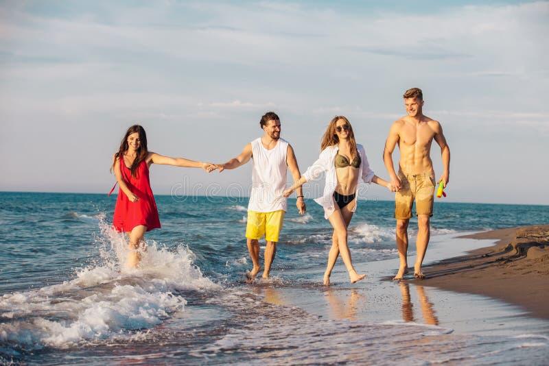 Amici insieme sul divertiresi della spiaggia immagine stock libera da diritti