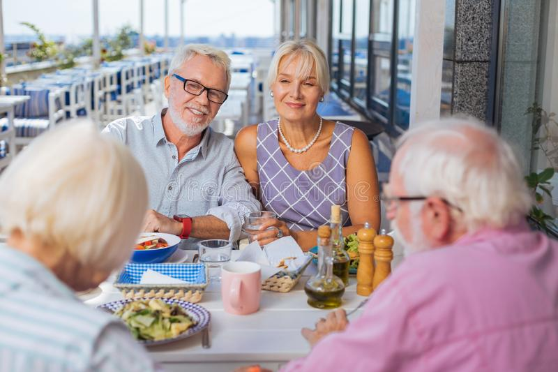 Amici invecchiati piacevoli che si incontrano insieme per il pranzo immagini stock