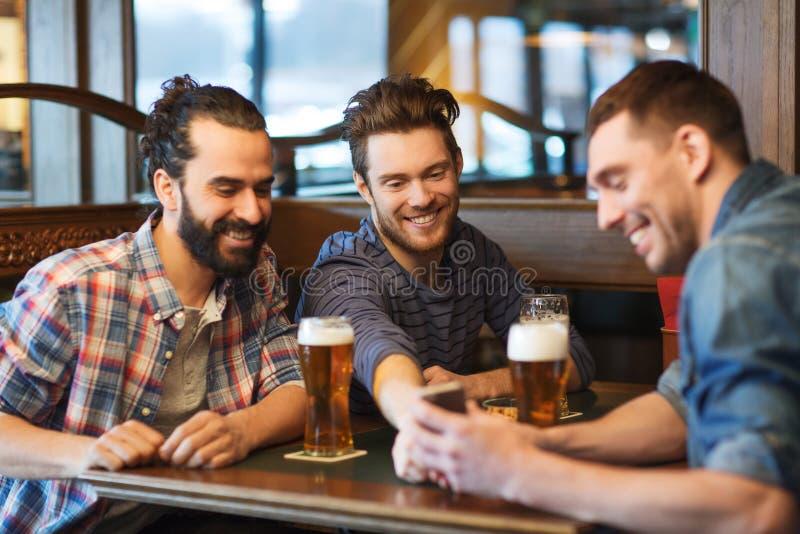 Amici maschii con la birra bevente dello smartphone alla barra fotografia stock libera da diritti
