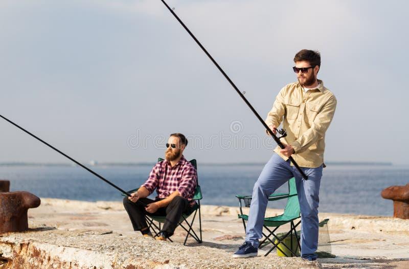 Amici maschii con le canne da pesca sul pilastro del mare fotografia stock libera da diritti