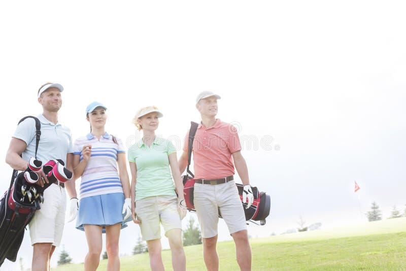 Amici maschii e femminili che stanno al campo da golf contro il chiaro cielo fotografia stock