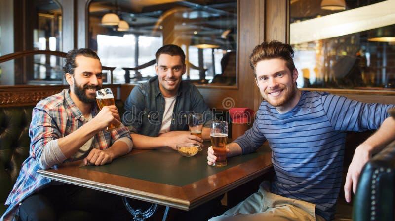 Amici maschii felici che bevono birra alla barra o al pub fotografia stock libera da diritti