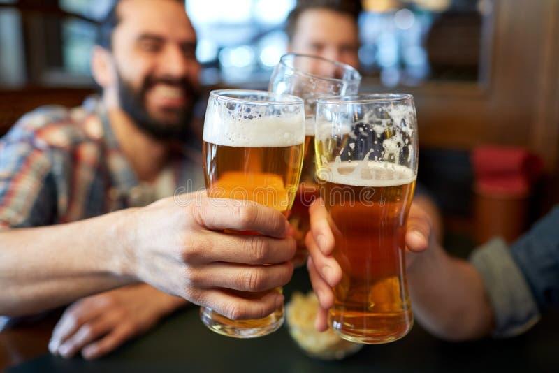 Amici maschii felici che bevono birra alla barra o al pub fotografie stock