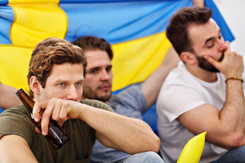 Amici maschii felici che incoraggiano e che guardano gli sport sulla TV fotografia stock