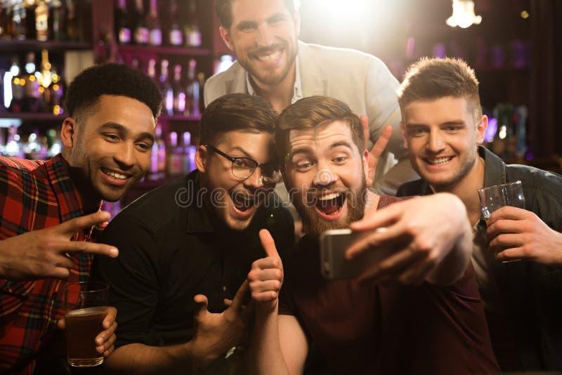 Amici maschii felici che prendono selfie e che bevono birra fotografie stock libere da diritti