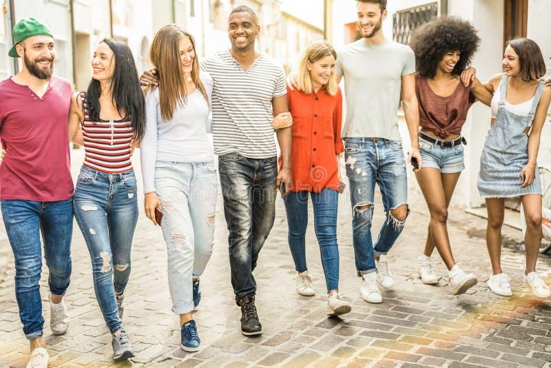 Amici millenari multirazziali che camminano e che parlano nel centro urbano immagini stock