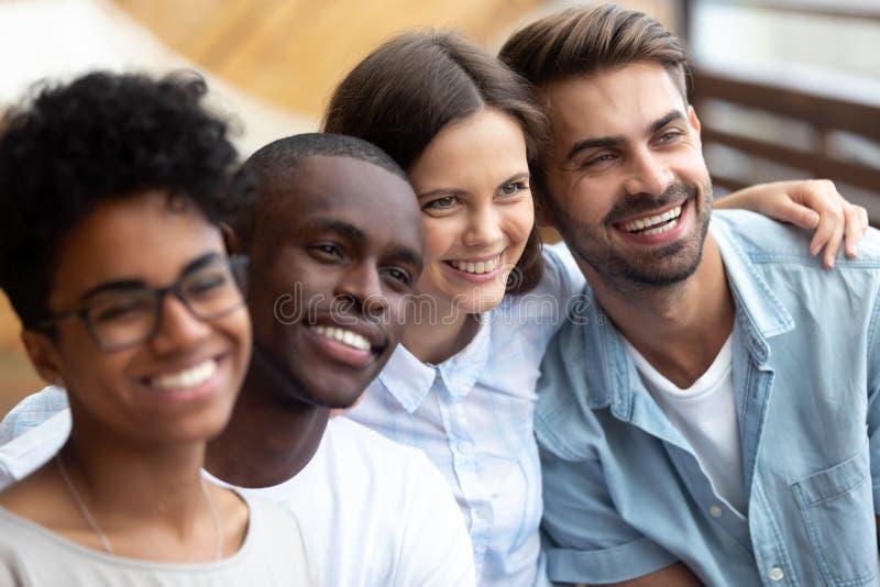 Amici multietnici felici che posano insieme per la foto vicino su immagine stock libera da diritti
