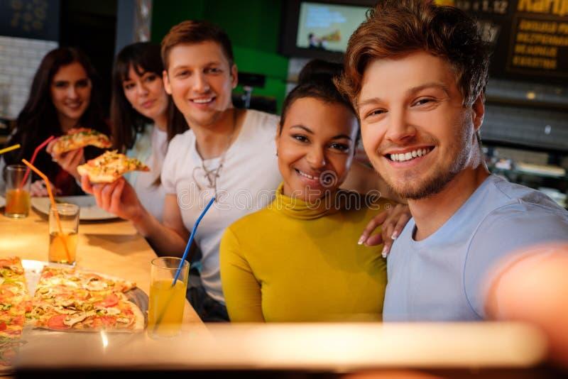Amici multirazziali allegri che prendono selfie in pizzeria fotografie stock