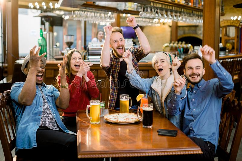 Amici multirazziali allegri divertendosi cibo nella pizzeria Stanno guardando emozionalmente la partita di calcio fotografia stock libera da diritti