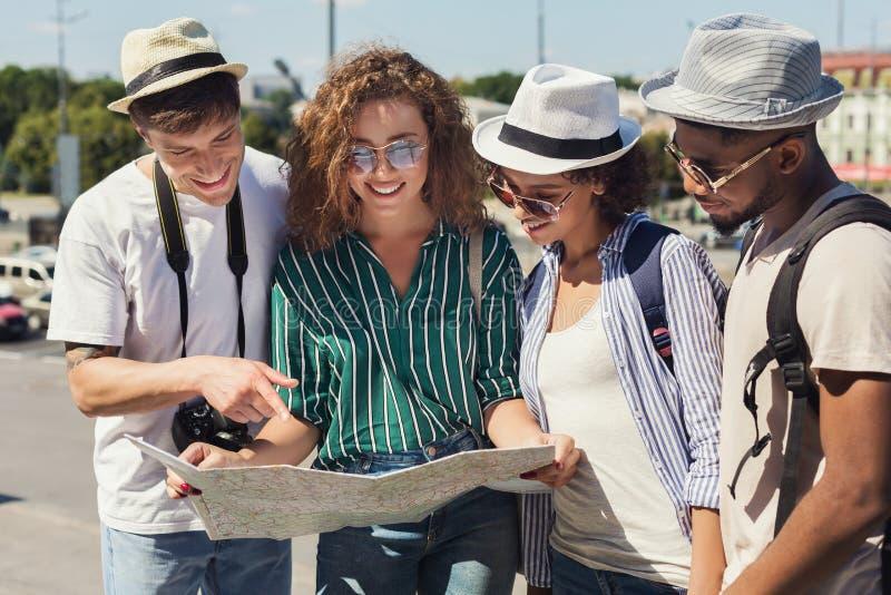 Amici multirazziali che cercano la direzione facendo uso della mappa della carta immagini stock