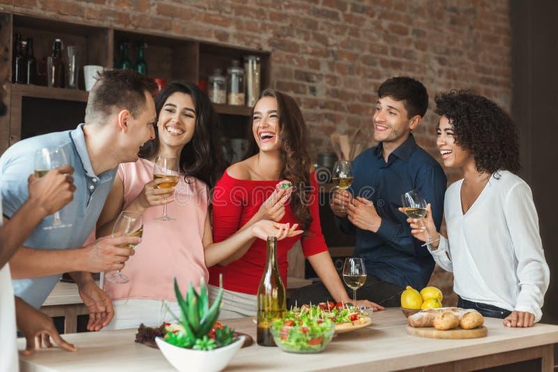 Amici multirazziali che godono di piccolo partito a casa immagine stock