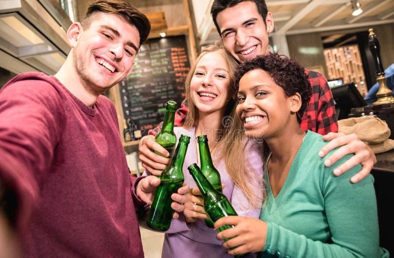 Amici multirazziali che prendono selfie e che bevono birra al pub operato della fabbrica di birra fotografia stock libera da diritti