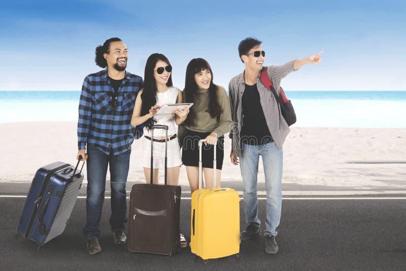 Amici multirazziali con la borsa sulla spiaggia fotografia stock libera da diritti