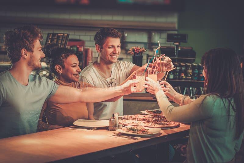 Amici multirazziali divertendosi cibo nella pizzeria fotografia stock libera da diritti