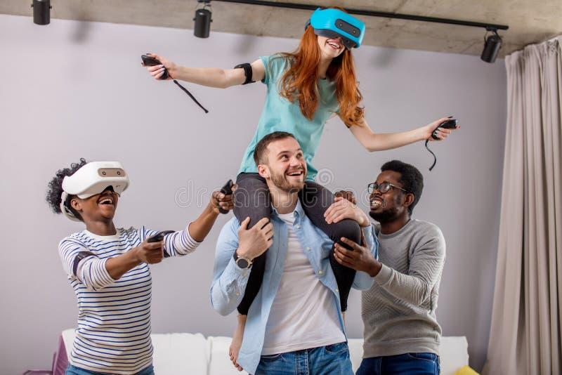 Amici multirazziali divertendosi e dando giro di a due vie alla donna in vetri del vr fotografia stock libera da diritti