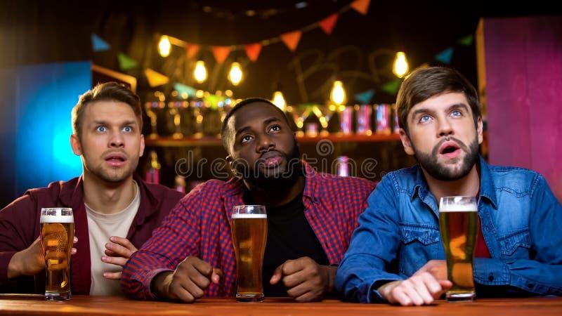 Amici multirazziali eccitati che guardano il canale di sport sedersi nel pub della birra, svago immagine stock libera da diritti