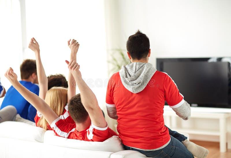 Amici o tifosi che guardano TV a casa fotografia stock libera da diritti
