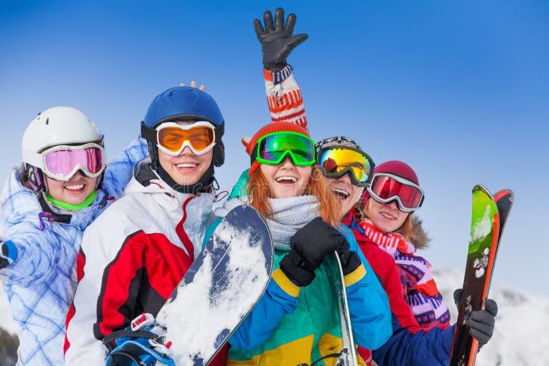 Amici positivi con gli snowboard e gli sci immagine stock