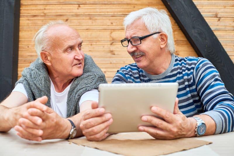 Amici senior che per mezzo della compressa di Digital immagine stock