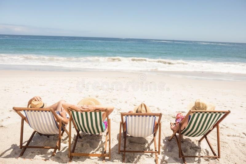 Amici senior che si siedono nella sedia di spiaggia immagine stock