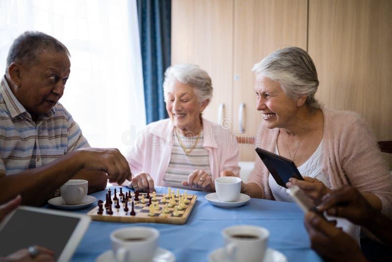 Amici senior felici che giocano scacchi mentre mangiando caffè fotografia stock libera da diritti