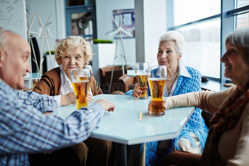 Amici senior riuniti in pub fotografia stock
