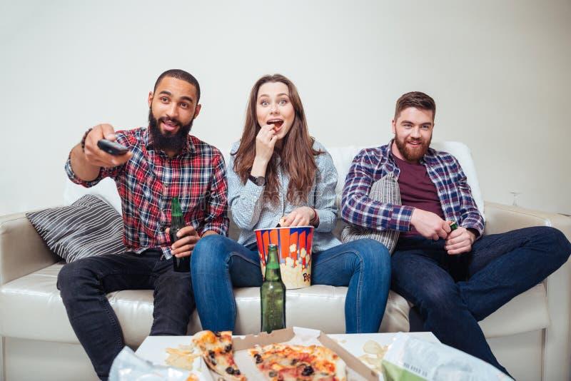 Amici sorpresi felici che guardano TV a casa insieme immagini stock libere da diritti