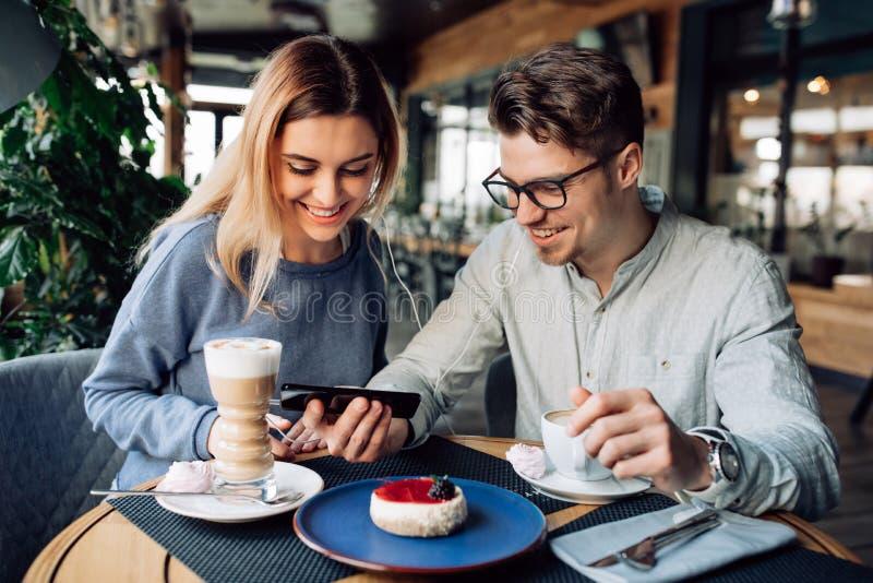 Amici sorridenti che guardano un film sullo smartphone, spendente tempo al caffè fotografie stock libere da diritti