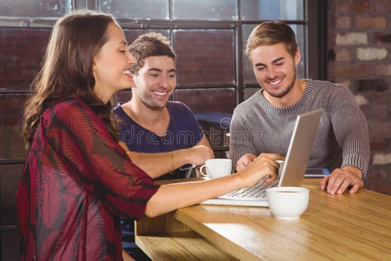Amici sorridenti che hanno caffè insieme ed esame del computer portatile immagini stock