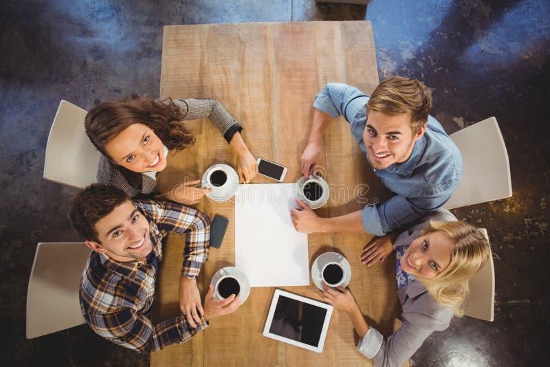 Amici sorridenti che si siedono e che bevono caffè fotografia stock