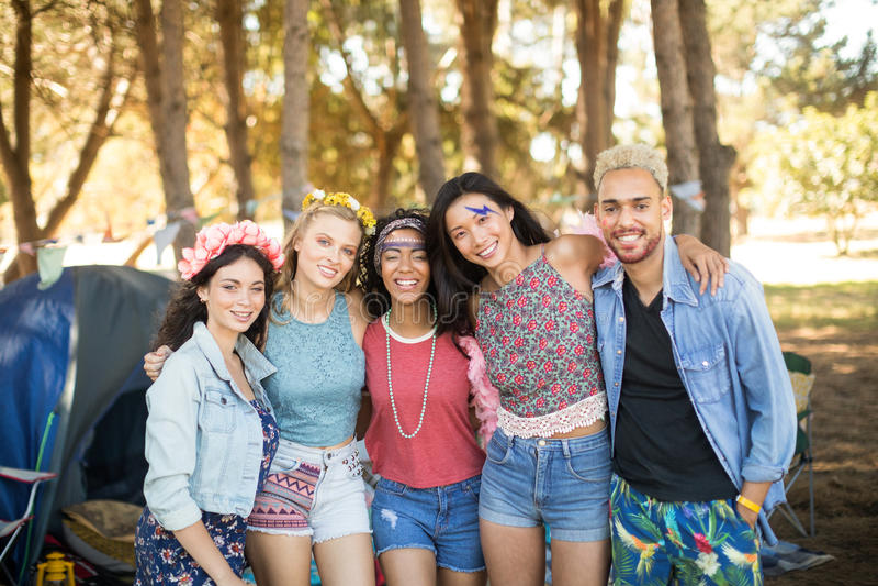 Amici sorridenti che stanno insieme al campeggio immagini stock