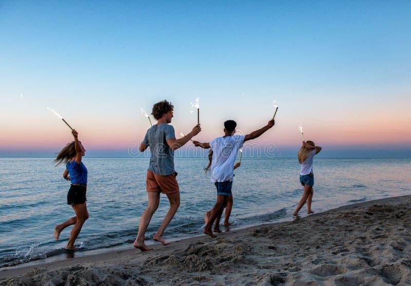 Amici sorridenti felici che corrono alla spiaggia con le candele scintillanti fotografia stock