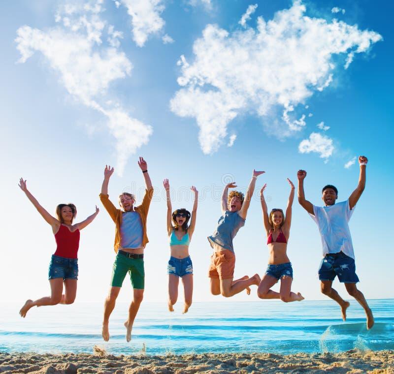 Amici sorridenti felici che saltano sopra un cielo blu con una mappa di mondo fatta delle nuvole fotografia stock libera da diritti