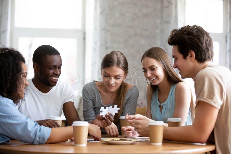 Amici sorridenti felici della corsa mista che montano il rompicapo di puzzle fotografie stock libere da diritti