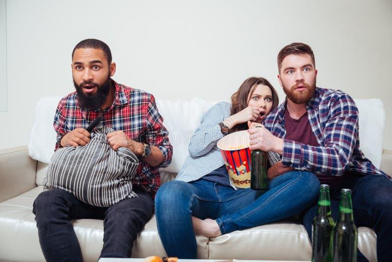Amici spaventati che si siedono sul sofà e sulla TV di sorveglianza fotografia stock