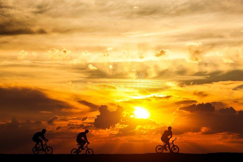 Amici su un viaggio della bici al tramonto Stile di vita attivo, hobby di riciclaggio fotografia stock